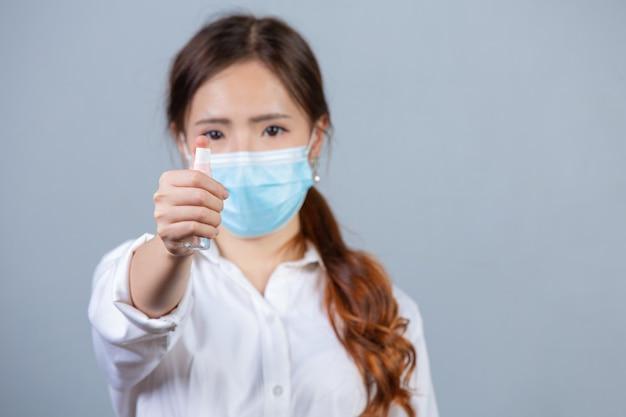 Portret młodej pięknej kobiety biznesu noszenie twarzy maska ręce stosując spray alkoholowy na szarej powierzchni