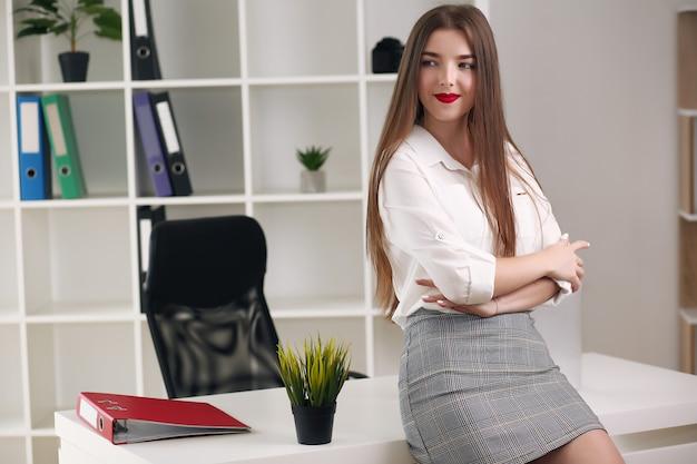 Portret młodej pięknej kobiety biznesu w biurze. skrzyżowane ręce.