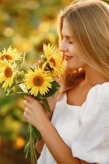 Portret młodej pięknej kobiety blondynka w polu słoneczników w świetle z tyłu. koncepcja wsi lato. kobieta i słoneczniki. letnie światło. piękno na świeżym powietrzu.