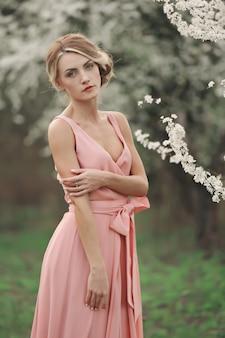 Portret młodej pięknej kobiety blondynka w różowej sukience w pobliżu kwitnących drzew o białych kwiatach w słoneczny dzień. wiosna, dziewczyna w pobliżu kwitnącego drzewa