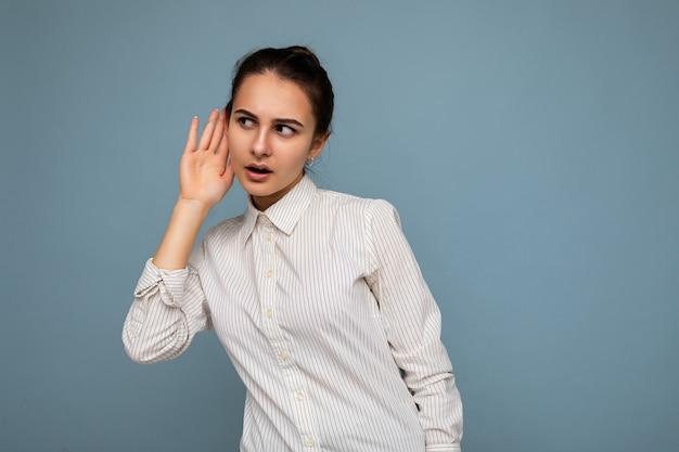 Portret młodej pięknej kobiety brunetka na sobie białą koszulę na białym tle ze szczerymi emocjami