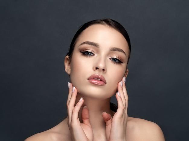 Portret młodej pięknej kobiety dotyka jej twarzy, oczyszczanie skóry, terapia spa, pielęgnacja skóry, kosmetologia i koncepcja chirurgii plastycznej