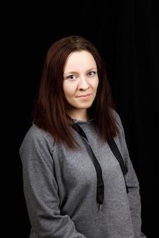Portret młodej pięknej kobiety fitness nosi bluzkę szary sport na czarnym tle.