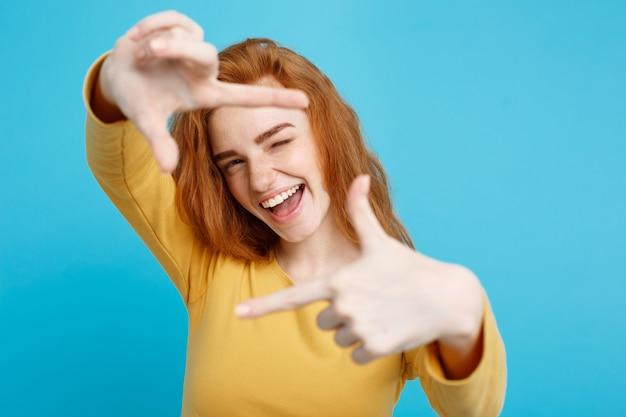 Portret młodej pięknej kobiety imbir z piegami radośnie uśmiechając się, tworząc ramkę z palcami na białym tle na białej ścianie kopii przestrzeni