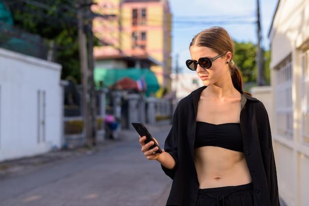 Portret młodej pięknej kobiety jako tajny agent na ulicach miasta na zewnątrz