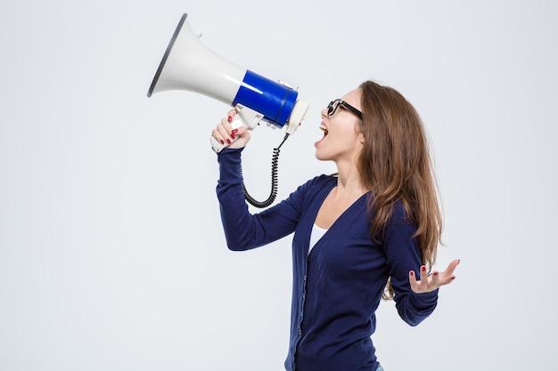 Portret młodej pięknej kobiety krzyczącej w głośniku na białym tle