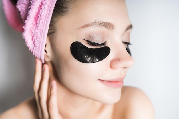 Portret młodej pięknej kobiety, która pielęgnuje skórę, po kąpieli, z ręcznikiem na głowie, uśmiechnięta, zamknęła oczy
