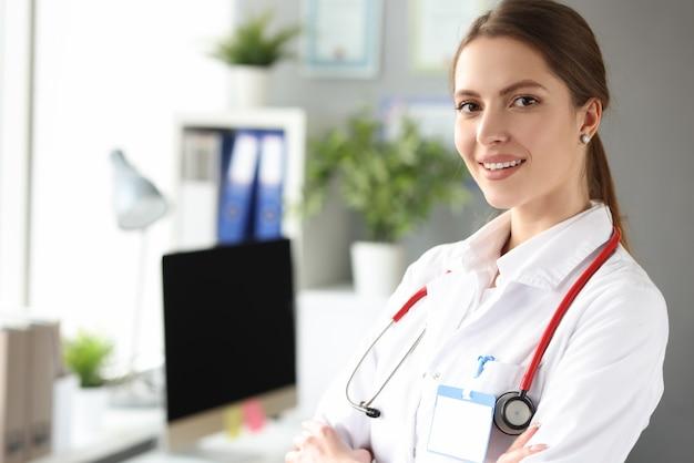 Portret młodej pięknej kobiety lekarz w białym fartuchu w biurze