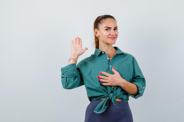 Portret młodej pięknej kobiety macha ręką na powitanie, trzymając rękę na klatce piersiowej w zielonej koszuli i patrząc na wesoły widok z przodu