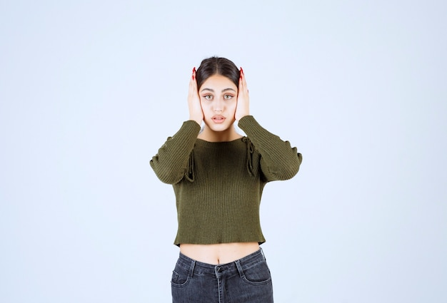 Portret młodej pięknej kobiety model stojący i trzymający głowę.