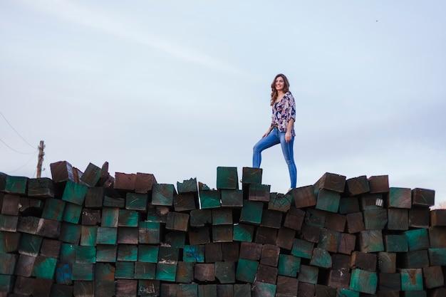 Portret młodej pięknej kobiety na sobie ubranie, stojąc na górze zielonych bloków drewnianych i uśmiechając się. styl życia na zewnątrz.