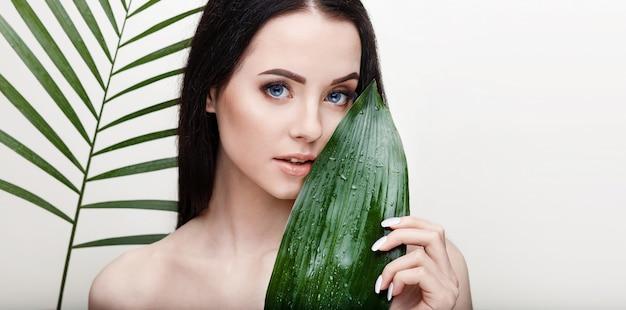 Portret młodej pięknej kobiety o zdrowej gładkiej skórze trzyma zielony tropikalny liść