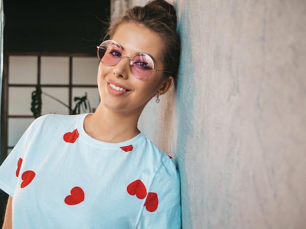 Portret młodej pięknej kobiety patrząc na kamery modna dziewczyna w swobodnej letniej białej koszulce i okularach przeciwsłonecznych śmieszna i pozytywna kobieta pozuje blisko szarej ściany w studiu