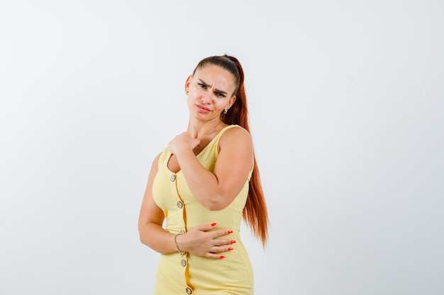 Portret młodej pięknej kobiety pozowanie stojąc w sukience i patrząc zdenerwowany widok z przodu