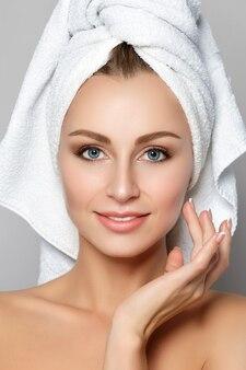 Portret młodej pięknej kobiety rasy kaukaskiej dotykając jej twarzy. oczyszczająca twarz, idealna skóra. terapia spa, pielęgnacja skóry, kosmetologia.