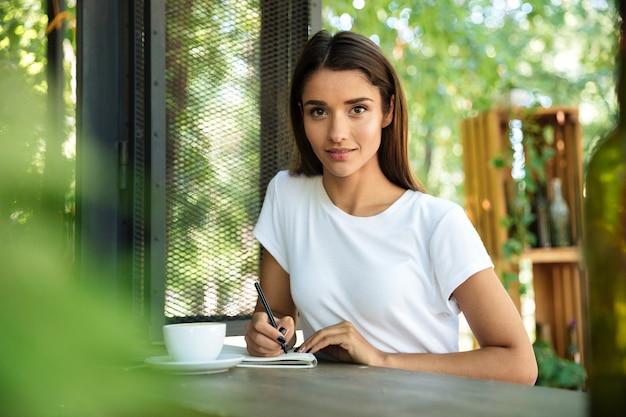 Portret młodej pięknej kobiety robienia notatek w podręczniku