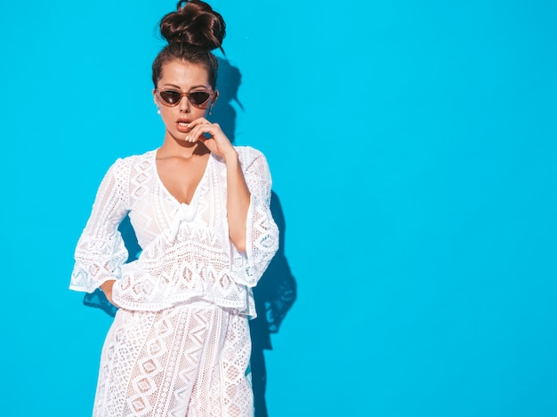 Portret młodej pięknej kobiety sexy z fryzura ghul. modna dziewczyna w swobodnym letnim białym garniturze hipster ubrania w okularach przeciwsłonecznych. gorący model odizolowywający na błękicie