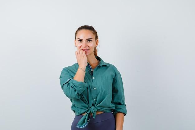 Portret młodej pięknej kobiety sprawdzającej zęby w zielonej koszuli i patrzącej niezdecydowany widok z przodu