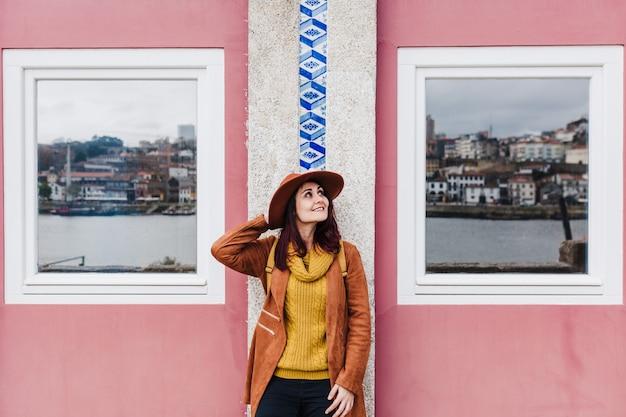 Portret młodej pięknej kobiety stojącej przy ścianie porto na sobie nowoczesny kapelusz, ciesząc się widokami. koncepcja podróży