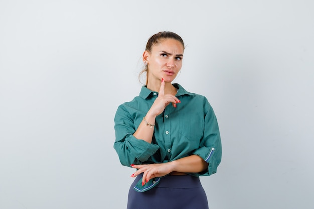 Portret młodej pięknej kobiety stojącej w myślącej pozie w zielonej koszuli i patrzącej zdziwiony widok z przodu