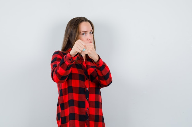 Portret młodej pięknej kobiety stojącej w pozie do walki w casualowej koszuli i patrzącej wściekle z przodu