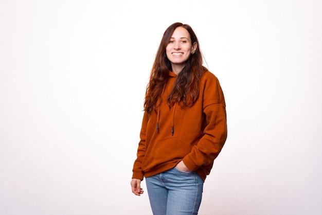Portret młodej pięknej kobiety stojącej z ręką w kieszeni i uśmiechając się do kamery