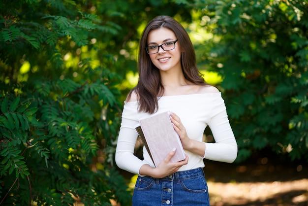 Portret młodej pięknej kobiety studenckiej z książkami