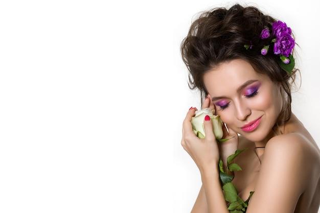 Portret młodej pięknej kobiety trzymającej białą różę z fioletowymi goździkami we włosach.
