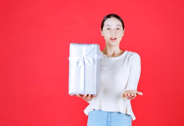 Portret młodej pięknej kobiety uśmiecha się i trzyma zapakowane pudełko na prezent