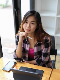 Portret młodej pięknej kobiety, uśmiechając się i patrząc w kamerę podczas pracy w wygodnym obszarze roboczym