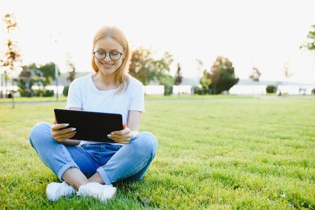 Portret młodej pięknej kobiety uśmiechający się z komputera typu tablet, na zewnątrz