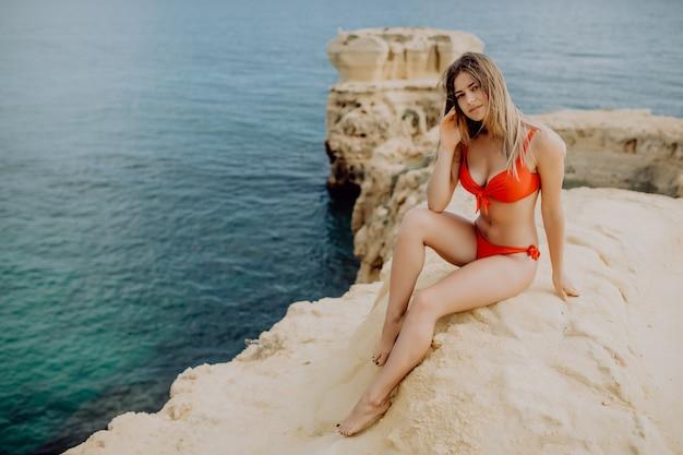 Portret młodej pięknej kobiety w czerwonym bikini siedzi na skałach w pobliżu niebiesko-zielonego czystego oceanu wody morskiej.