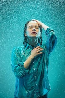 Portret młodej pięknej kobiety w deszczu