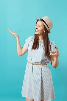Portret młodej pięknej kobiety w niebieskiej sukience, kapelusz trzymając szklankę czystej świeżej czystej wody na białym tle na niebieskim tle. zdrowy styl życia, pojęcie szczere emocje ludzi. wskazując dłoń na przestrzeni kopii.