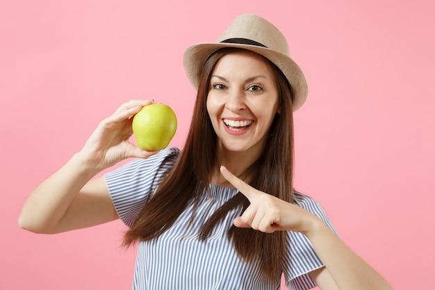 Portret młodej pięknej kobiety w niebieskiej sukience, letni słomkowy kapelusz gospodarstwa, jedzenie zielonych świeżych owoców jabłka na białym tle na różowym tle. zdrowy styl życia, ludzie, koncepcja szczere emocje. skopiuj miejsce.
