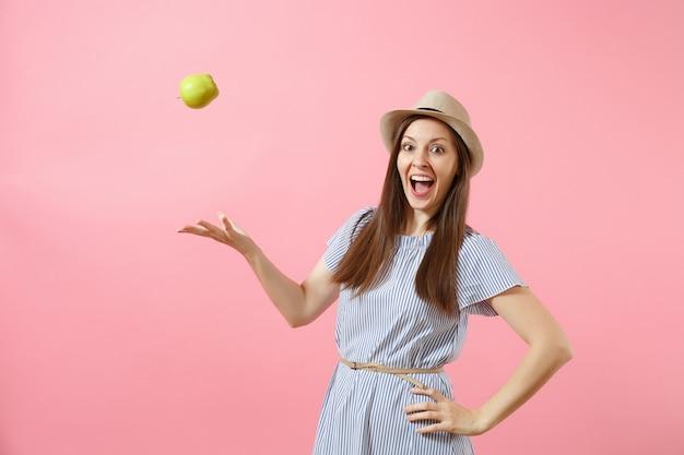 Portret młodej pięknej kobiety w niebieskiej sukience, letni słomkowy kapelusz gospodarstwa, rzucać zielone świeże owoce jabłko na białym tle na różowym tle. zdrowy styl życia, ludzie, koncepcja szczere emocje. skopiuj miejsce
