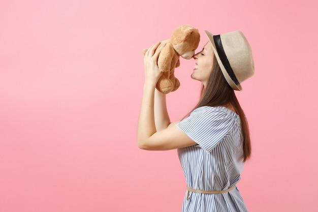 Portret młodej pięknej kobiety w niebieskiej sukience, letni słomkowy kapelusz trzymając pluszową zabawkę pluszowego misia na białym tle na różowym tle. ludzie, szczere emocje, koncepcja stylu życia. powierzchnia reklamowa. skopiuj miejsce.