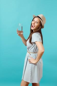 Portret młodej pięknej kobiety w niebieskiej sukience, trzymając kapelusz i pijąc czystą świeżą czystą wodę ze szkła na białym tle na niebieskim tle. zdrowy styl życia, pojęcie szczere emocje ludzi. skopiuj miejsce.