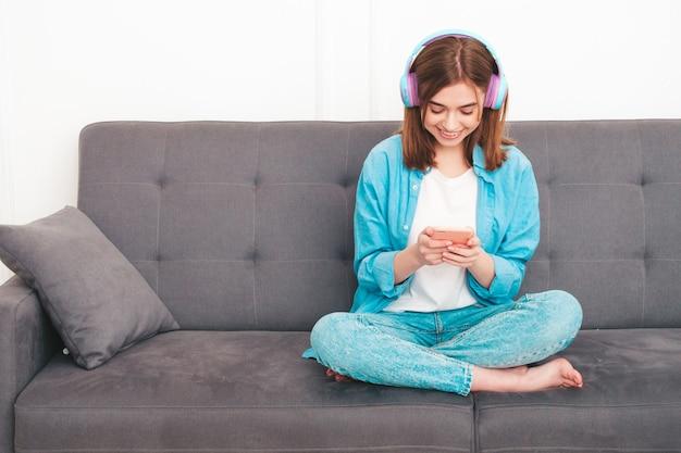 Portret młodej pięknej kobiety w stylowe ubrania. beztroska kobieta siedząca na kanapie w eleganckim mieszkaniu lub pokoju hotelowym w białym wnętrzu