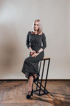Portret młodej pięknej kobiety w świetle miga. piękna blondynki kobieta w czerni sukni
