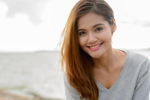 Portret młodej pięknej kobiety z azji przed malowniczym widokiem na jezioro i niebo w przyrodzie