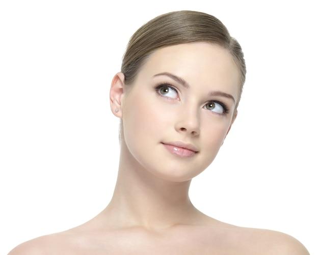Portret młodej pięknej kobiety z czystą skórą, patrząc na biel