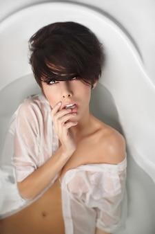 Portret młodej pięknej kobiety z krótkimi włosami, ciesząc się w kąpieli w białej koszuli mężczyzn dotykając warg