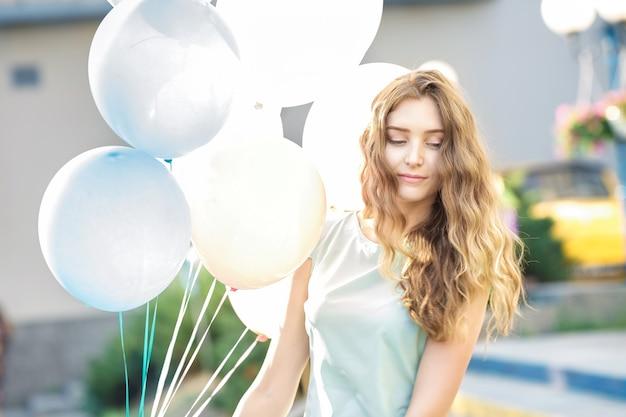 Portret młodej pięknej kobiety z latającymi wielokolorowymi balonami w mieście