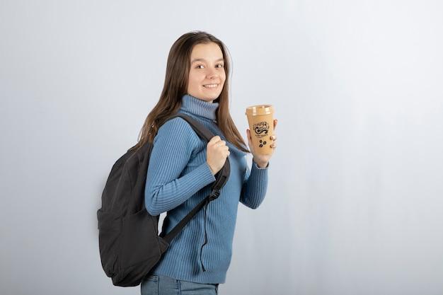 Portret młodej pięknej kobiety z plecakiem trzymając filiżankę kawy.