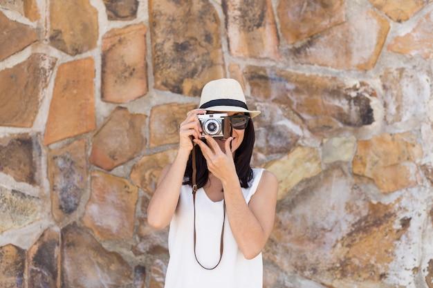 Portret młodej pięknej kobiety z rocznika kamery na tle kamienia. ona ma na sobie kapelusz i okulary przeciwsłoneczne.