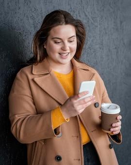 Portret młodej pięknej kobiety za pomocą telefonu komórkowego