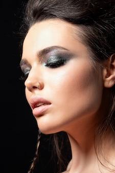 Portret młodej pięknej kobiety ze srebrnymi oczami smokey makijaż. modelka pozuje na czarnym tle