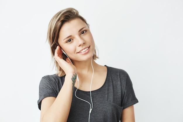 Portret młodej pięknej marzycielskiej dziewczyny słuchania muzyki w słuchawkach uśmiecha się.
