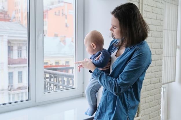 Portret młodej pięknej matki i syna malucha, kobieta trzyma dziecko w ramionach stojących w domu w pobliżu okna, miejsce